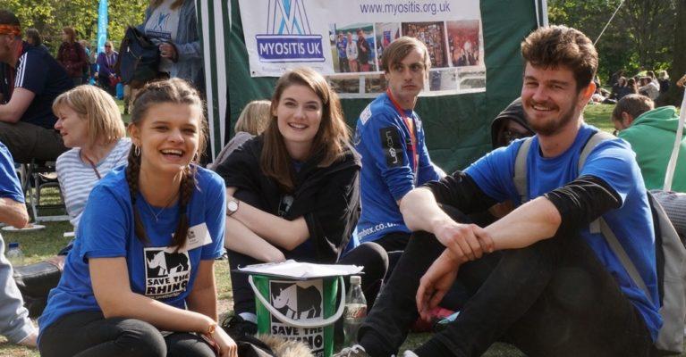 Three smiling events volunteer sitting down at the London Marathon picnic