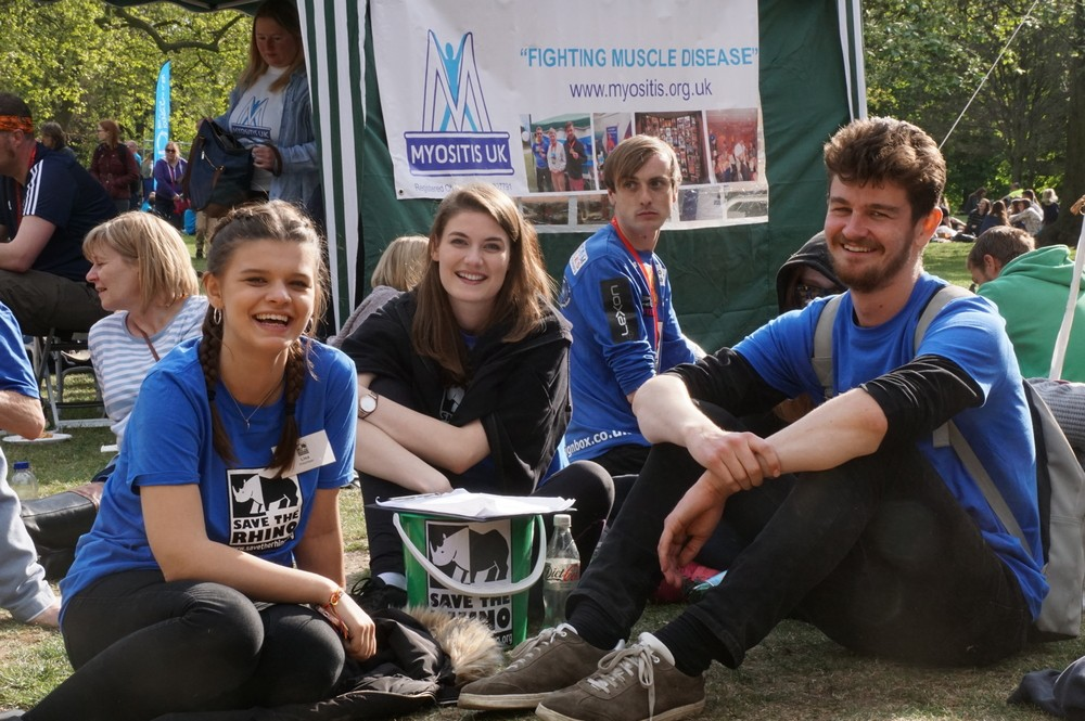 Three smiling events volunteer sitting down at the London Marathon picnic