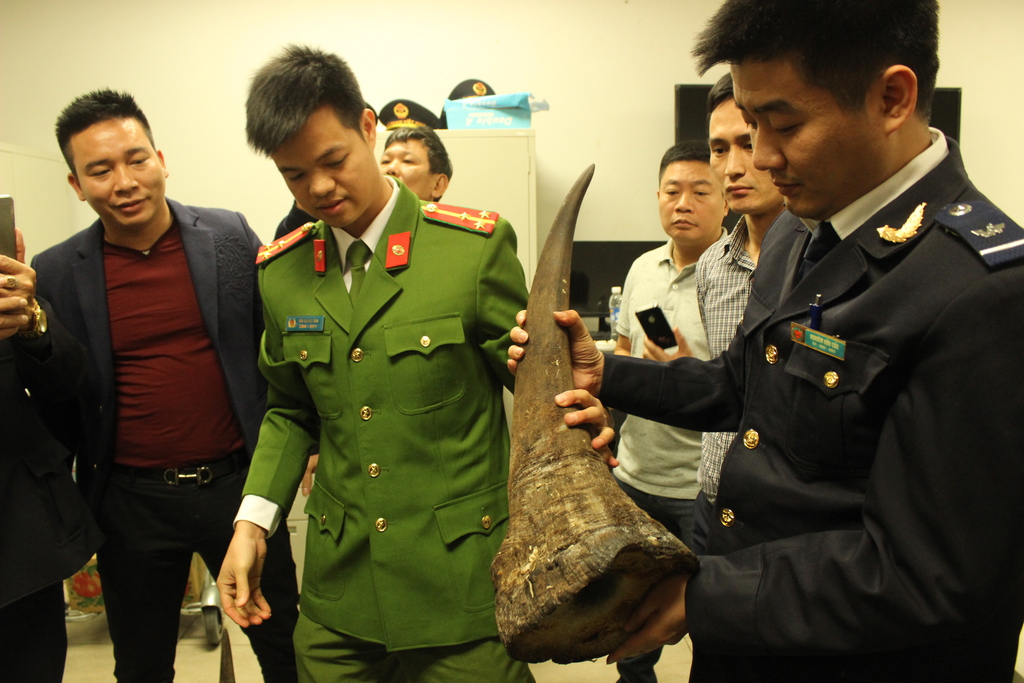 Image shows two Vietnamese officers showing seized rhino horn.