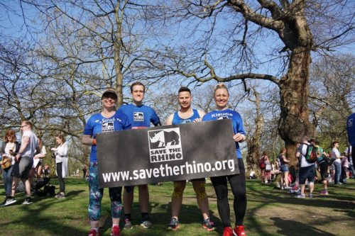 Image of four Save the Rhino runners before the 2018 London Marathon, holding a sign.