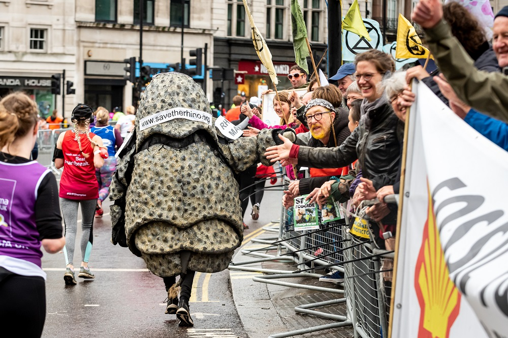 Rhino costume runner high fives spectators at the Royal Parks Half Marathon