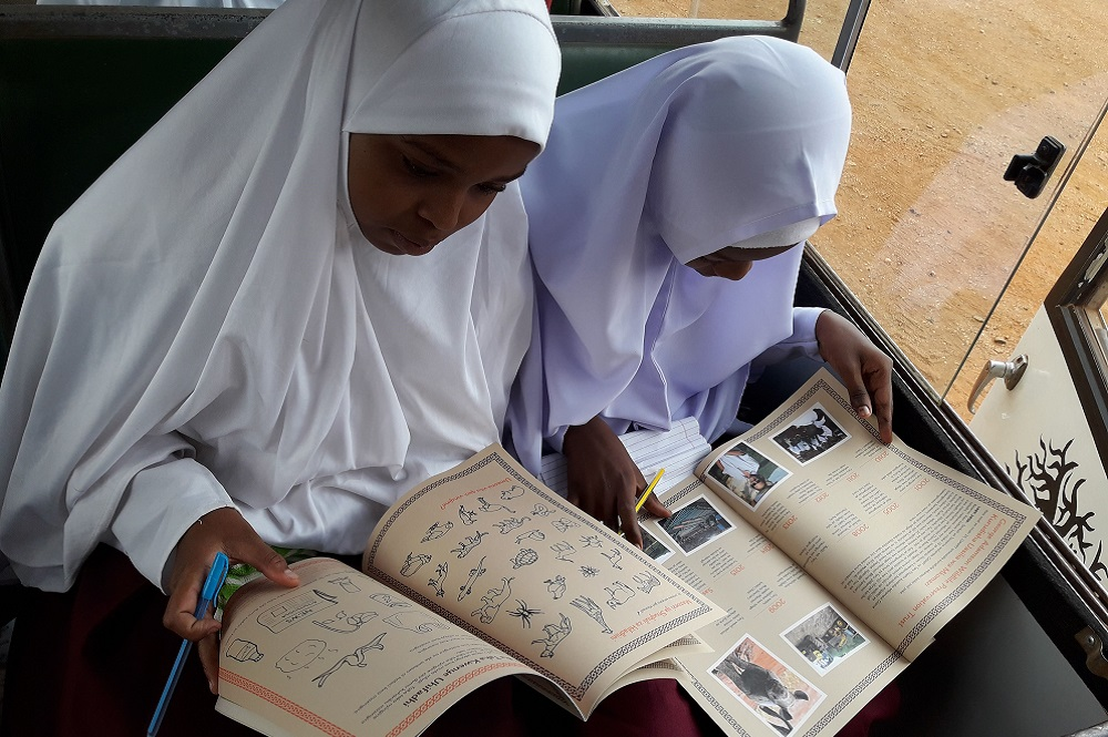 Image of two girls looking into rhino conservation textbooks.