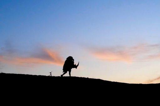 Silhouette of rhino costume running across the horizon